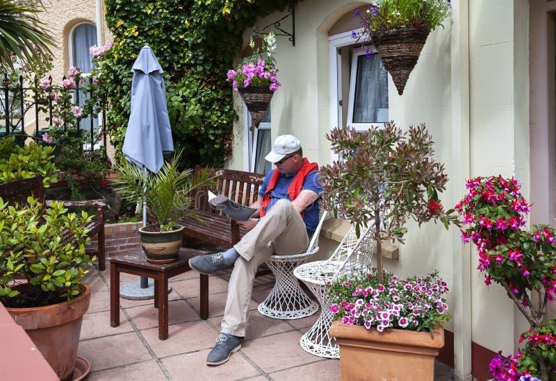 Läs- tidskrift för man i hemträdgård royaltyfri foto