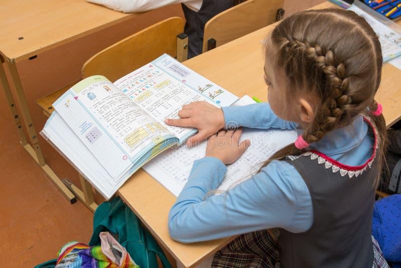 Läs- villkorproblem för skolflicka i läroboken royaltyfri bild