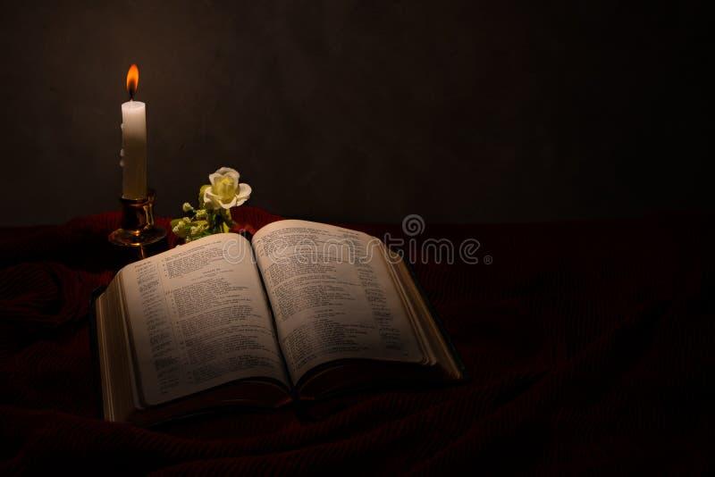 Läsa bibeln under stearinljusljuset royaltyfria bilder