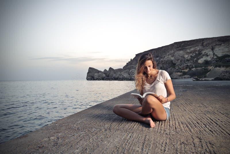 Läsa en bok på stranden arkivbilder