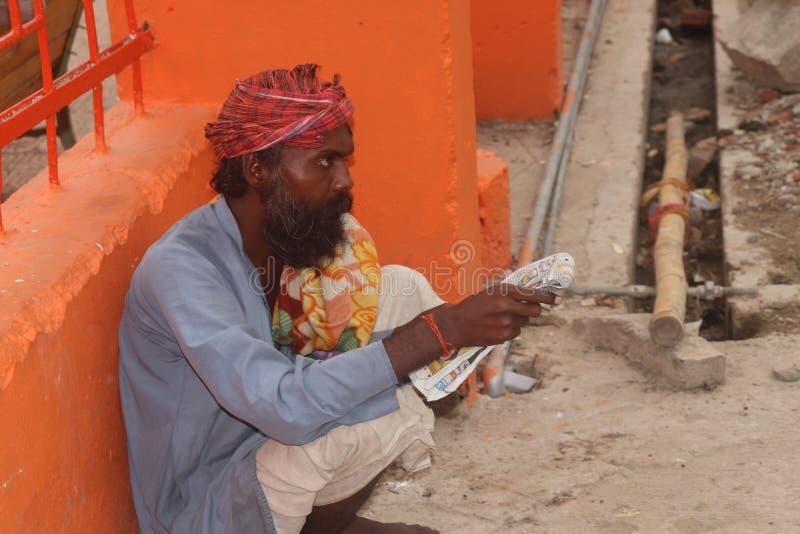 Läsa för gamal man som är pepar i allahabad Indien arkivbilder