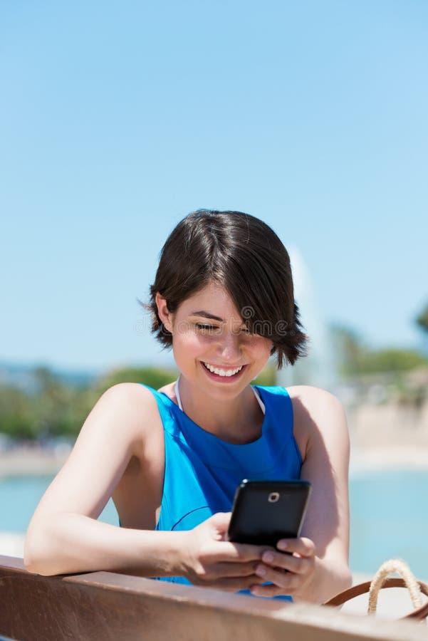 Läsa för kvinna sms på hennes mobil arkivbild