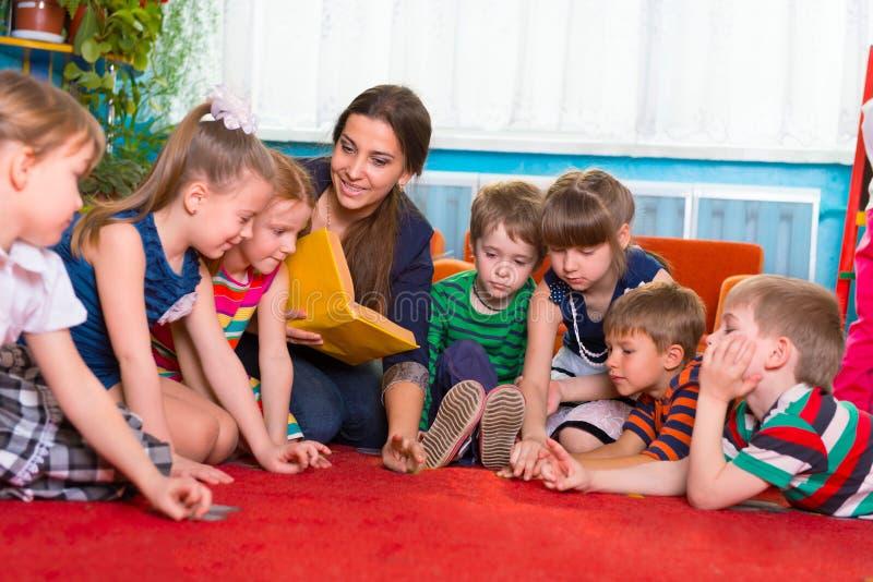 Läsa till barn på dagiset royaltyfria foton