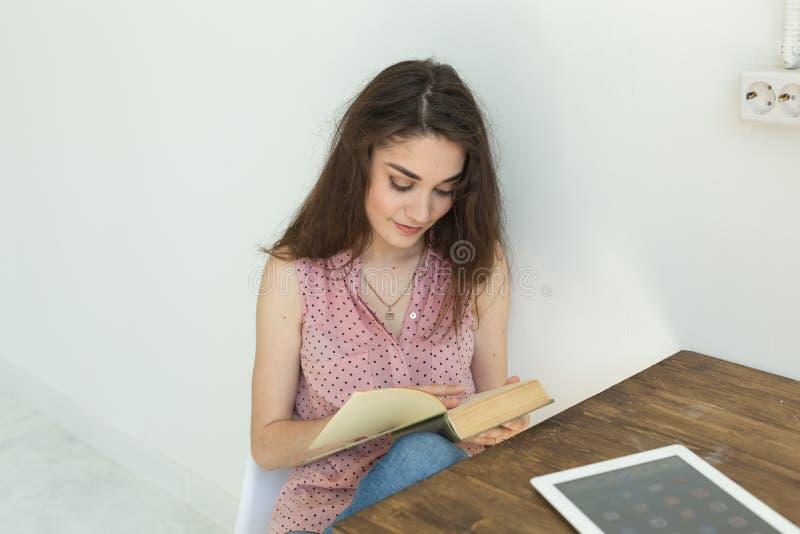 Läsa utbildning, kultur, folkbegrepp - den unga studentkvinnan läser en bok, medan hon sitter på vit stol royaltyfria bilder