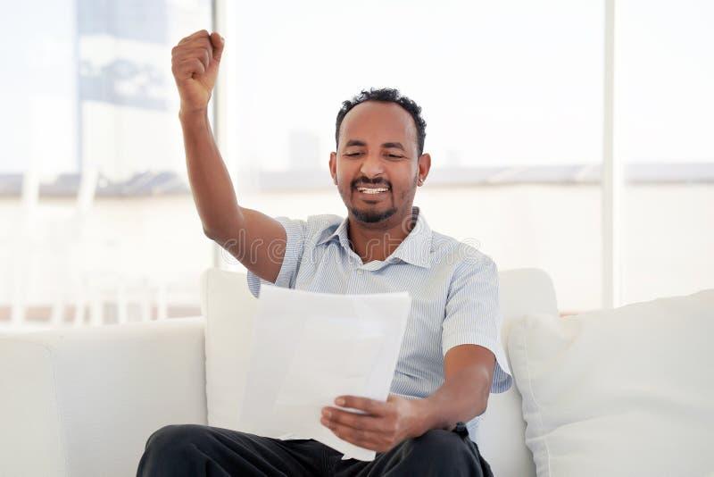 Läsande goda nyheter för lycklig entreprenörman i en bokstav på soffan i hem arkivbilder
