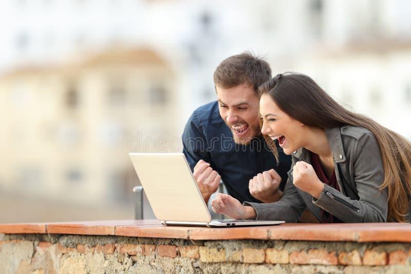 Läsande online-goda nyheter för upphetsade par på bärbara datorn arkivbild