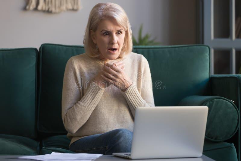 Läsande oväntad nyheterna för chockad grå haired mogen kvinna på bärbara datorn arkivfoto