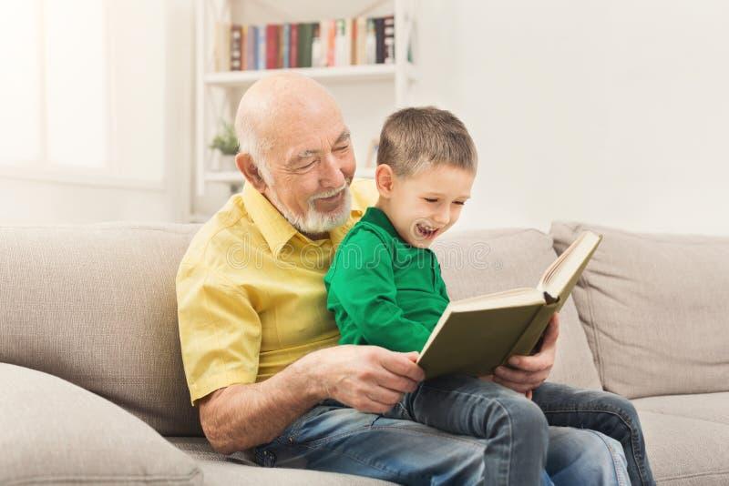 Läsebok för hög man för hans barnbarn royaltyfria foton