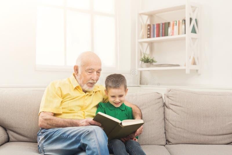 Läsebok för hög man för hans barnbarn royaltyfri bild