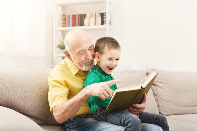 Läsebok för hög man för hans barnbarn arkivbild