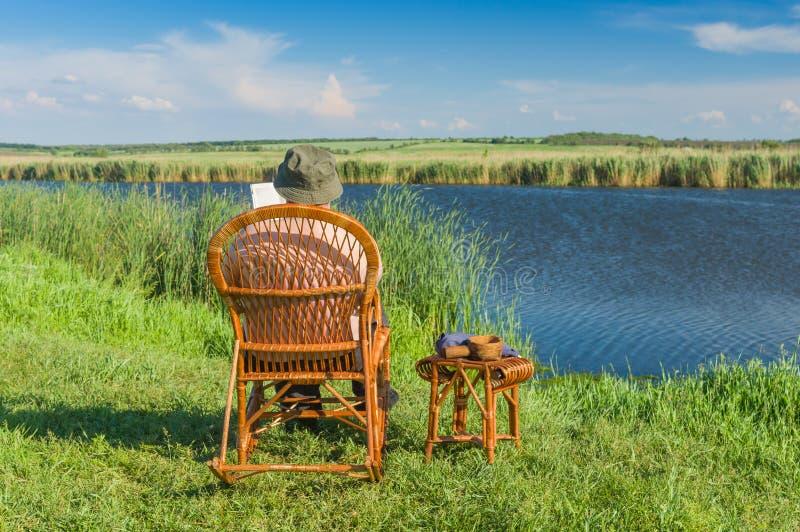 Läsebok för hög man, medan sitta i den vide- gungstolen på en flodstrand arkivfoton