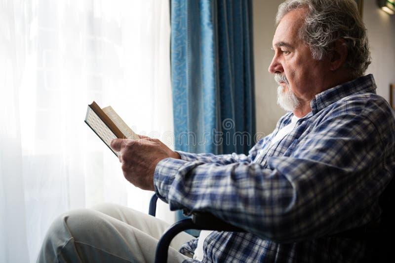 läsebok för hög man, medan sitta på rullstolen i vårdhem royaltyfria foton