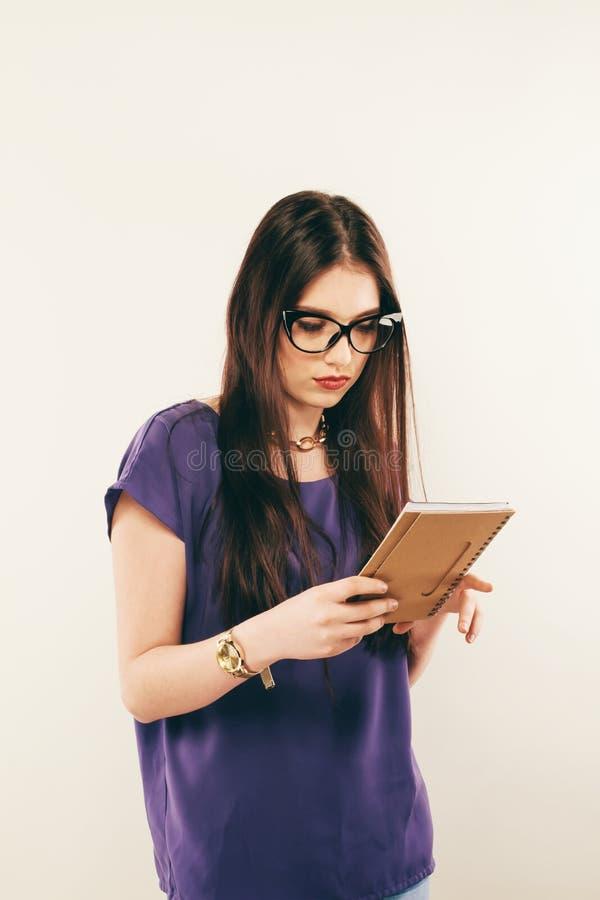 Läsebok för studentflicka uppmärksamt, fritt utrymme Stående av den unga kvinnan i exponeringsglas som försiktigt in studing mate arkivfoto