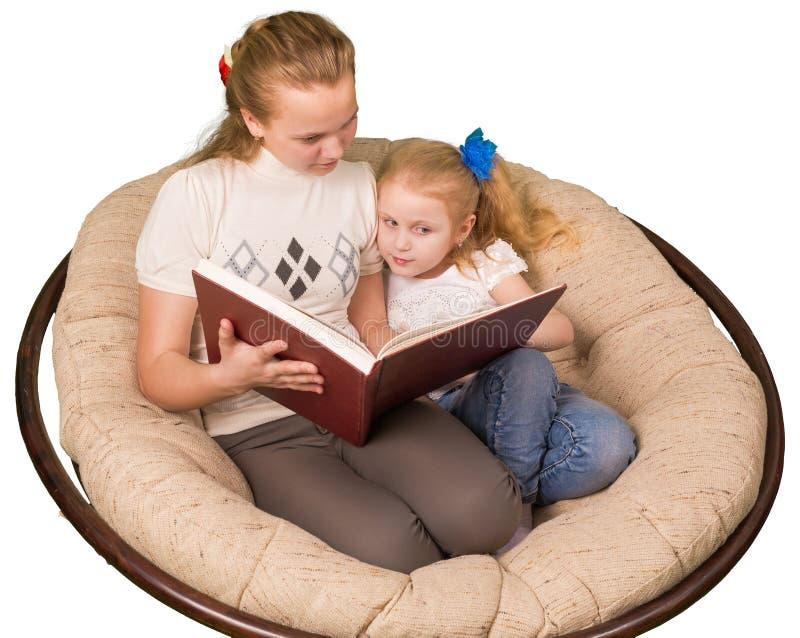 Läsebok för två flickor som isoleras på vit royaltyfri foto