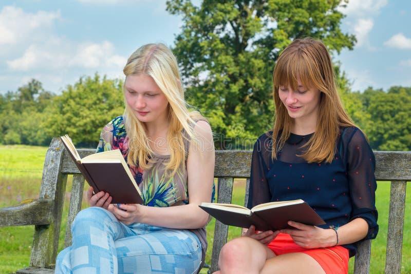Läsebok för två holländsk tonårs- flickor på bänk utanför royaltyfri bild