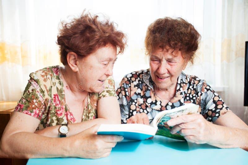Läsebok för två pensionärer hemma fotografering för bildbyråer