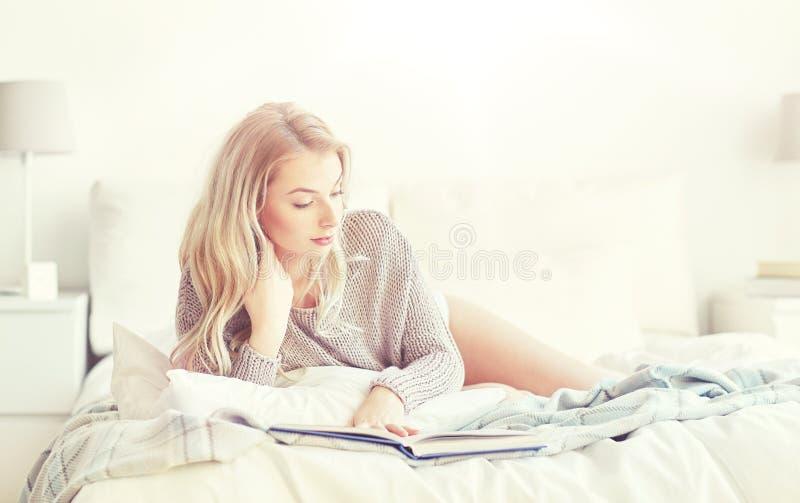 Läsebok för ung kvinna i säng hemma royaltyfri fotografi