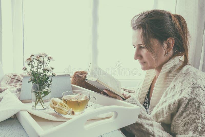 Läsebok för ung kvinna nära fönstret royaltyfri foto