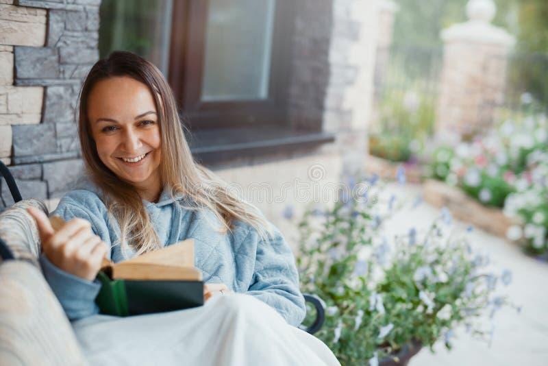Läsebok för ung kvinna och le bredvid härligt stort hus arkivfoton
