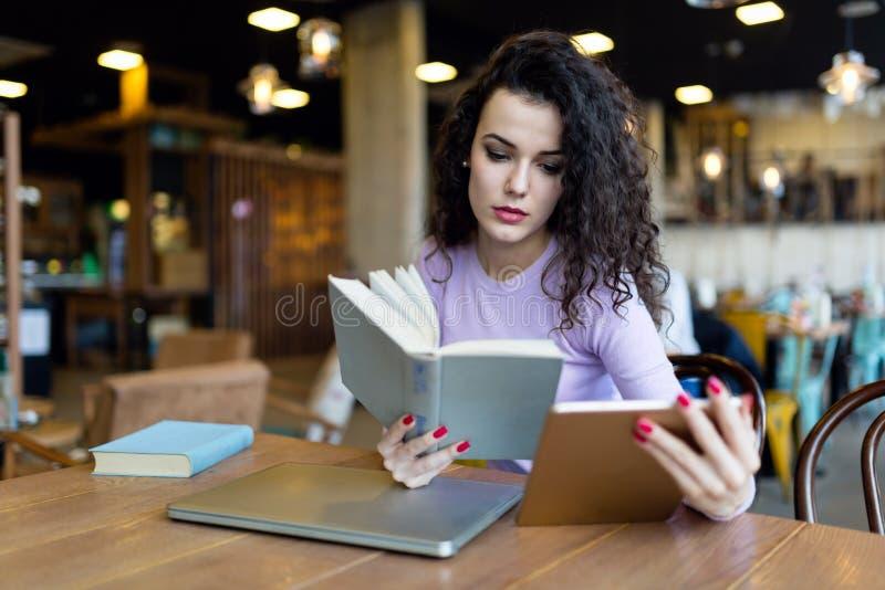 Läsebok för ung kvinna och rymmaminnestavla arkivfoto
