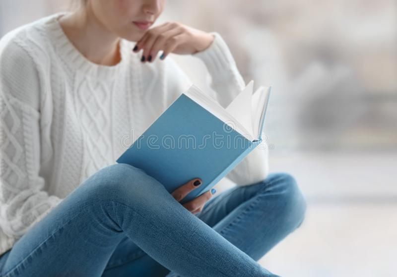 Läsebok för ung kvinna på fönsterbräda hemma fotografering för bildbyråer