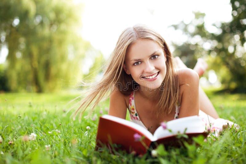 Läseboken för den unga kvinnan på parkerar att ligga ner på gräs arkivfoton