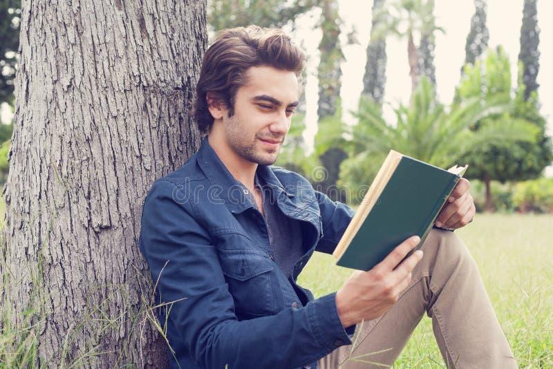 Läseboken för den unga mannen parkerar in arkivfoto