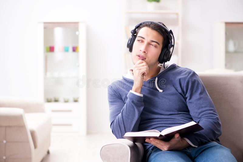 Läseboken för ung man och lyssna till talboken arkivbild