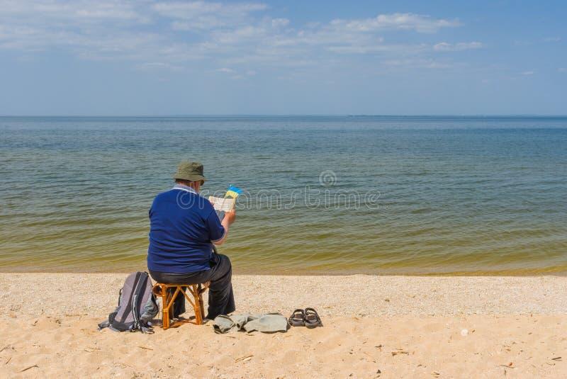 Läseboksammanträde för hög man på en strand arkivfoton