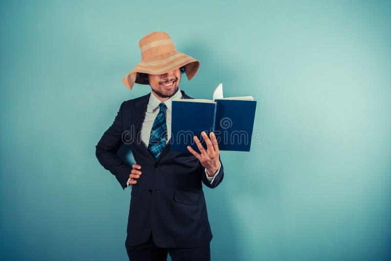 Läser den bärande strandhatten för affärsmannen arkivbilder