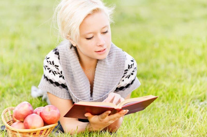 läser den charmiga flickan för boken arkivfoto