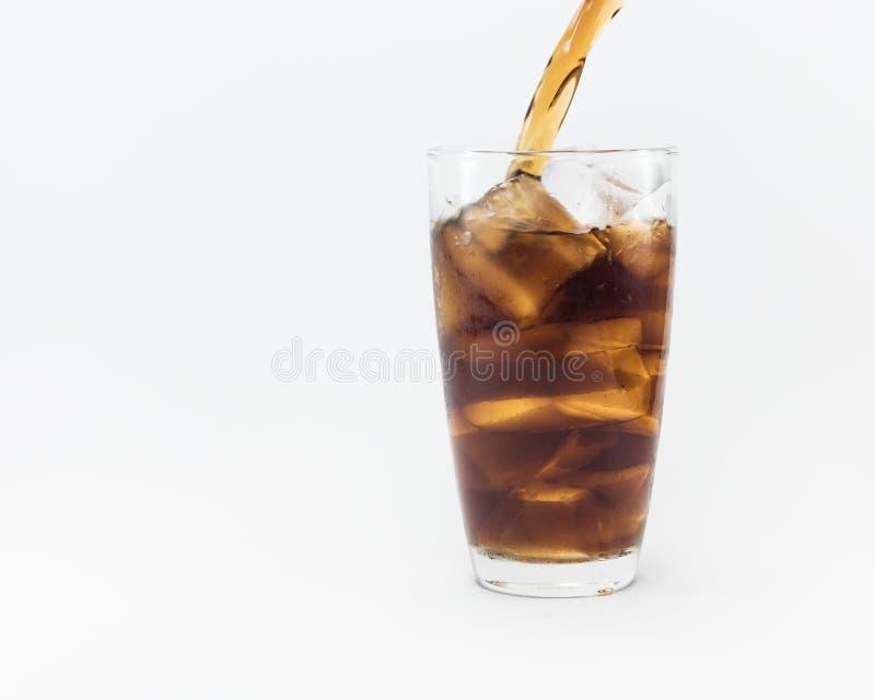 Läsk som häller från en plast- flaska in i ett exponeringsglas royaltyfria bilder