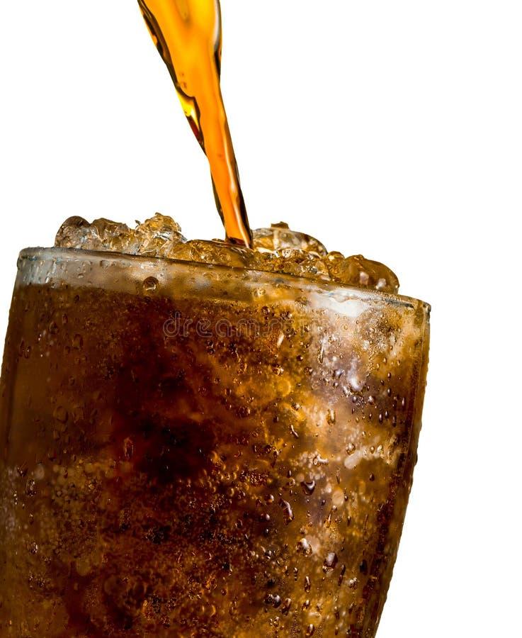 Läsk som häller till exponeringsglas med is som isoleras på vit backgroun arkivfoton