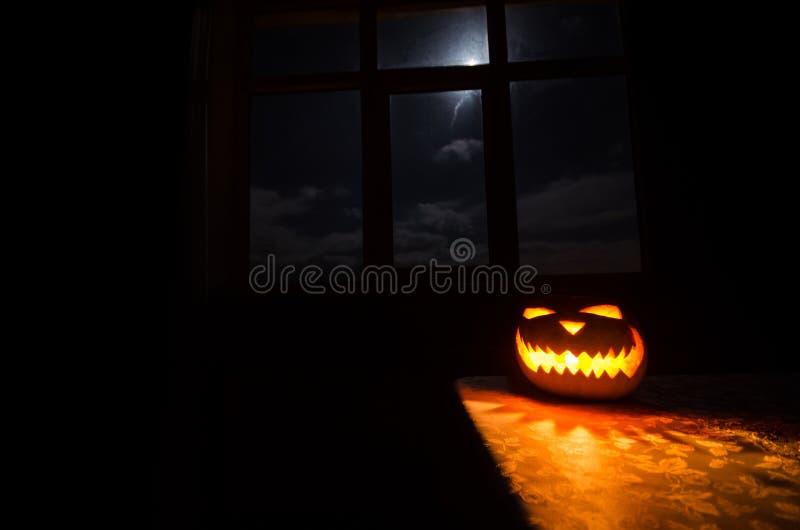 Läskig allhelgonaaftonpumpa i det mystiska husfönstret på natt- eller halloween pumpa i natt på rum med det blåa fönstret Symbol  royaltyfria bilder