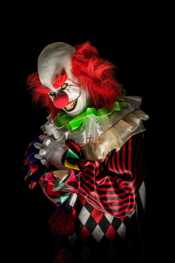 Läskig clown på en mörk bakgrund arkivbilder