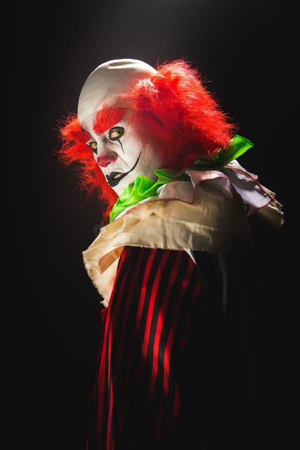 Läskig clown på en mörk bakgrund royaltyfri bild
