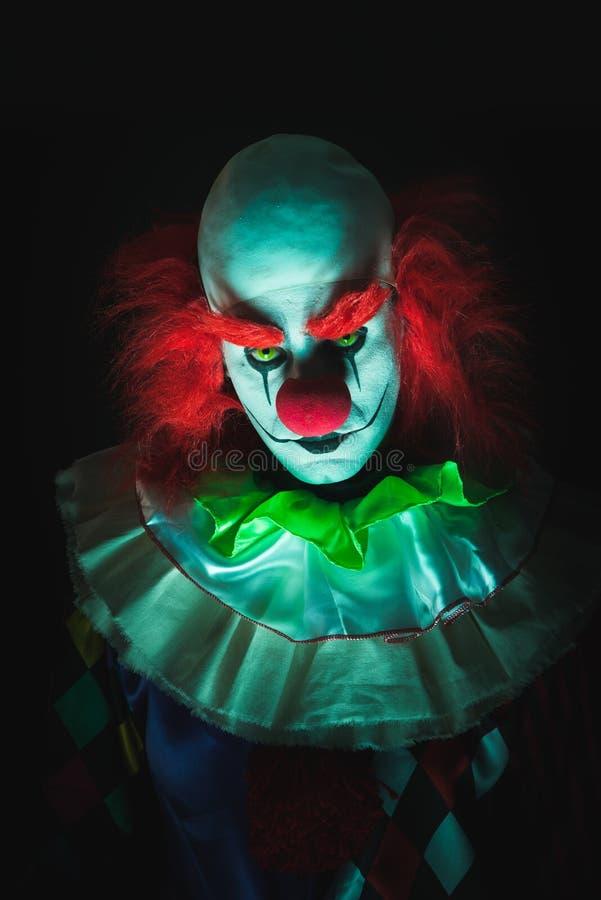 Läskig clown på en mörk bakgrund royaltyfri foto