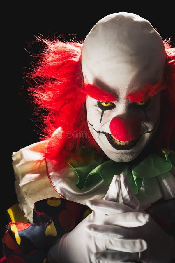 Läskig clown på en mörk bakgrund arkivbild