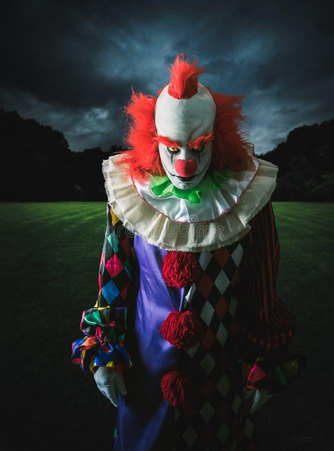 Läskig clown på en mörk bakgrund arkivfoto