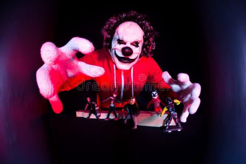 Läskig halloween clown i röd dräkt på svart bakgrund royaltyfri bild