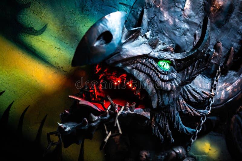 Läskig mörk och glödande drakehuvudskulptur royaltyfria foton