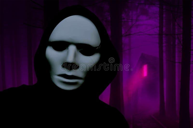 Läskig maskerad person för allhelgonaafton som bär ett huvanseende i en spökeskog med ett spökat hus i bakgrunden arkivfoto