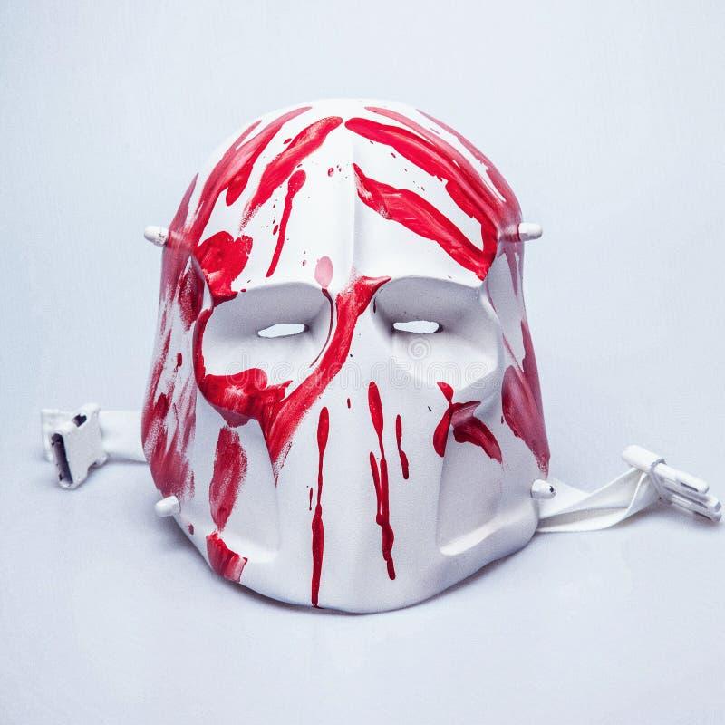 Läskig maskering som täckas med röd målarfärg/blod arkivbild