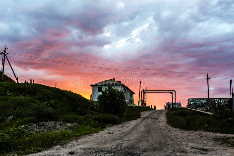 Läskig och ruskig solnedgång Förstört gammalt övergett stenhus i byn Teriberka i det Kolsky området av Murmansk Oblast, Ryssland royaltyfri foto