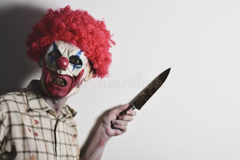 Läskig ond clown med en stor kniv arkivfoton