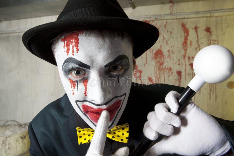 Läskig ond clown som bär en plommonstop på väggen royaltyfri foto