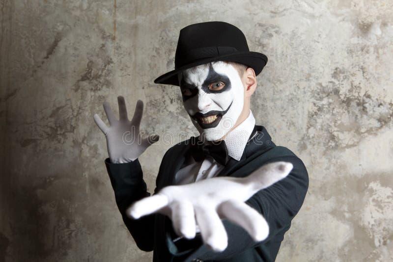 Läskig ond clown som bär en plommonstop på väggen royaltyfri fotografi