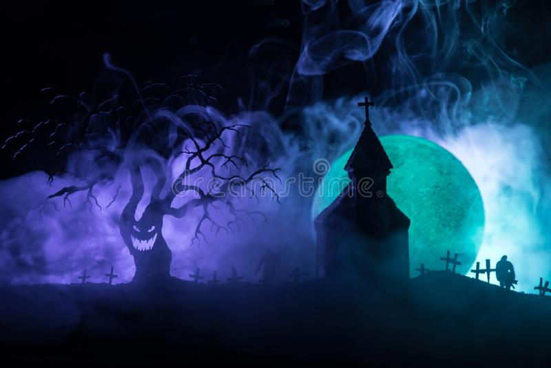 Läskig sikt av levande död på död för måne, kyrklig och spöklik för kyrkogård molnig himmel för träd, med dimma, fasaallhelgonaaf royaltyfri bild