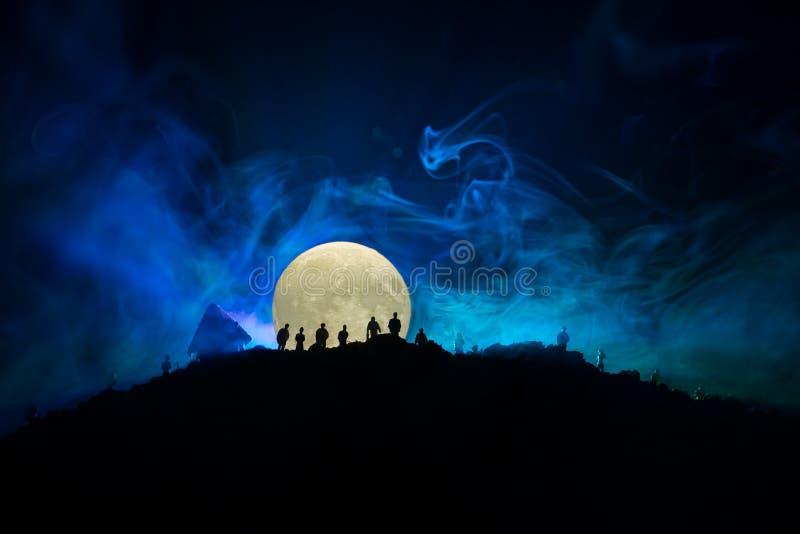 Läskig siktsfolkmassa av levande död på kullen med spöklik molnig himmel med dimma och resningfullmånen Konturgrupp av levande dö arkivbilder