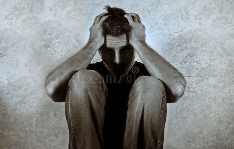 Läskig svartvit stående av den desperata mannen som gråter det hemmastadda golvet för ledset sammanträde i skuggig och dramatisk  royaltyfri foto